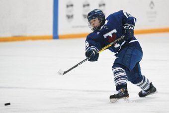 Photo of Varsity Blues' hockey player shooting a hockey puck.