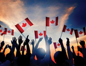 Sunset shot of hands in the air, waving Canadian flags