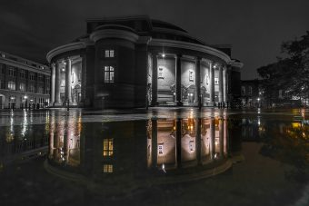 Photo by Bryan Li: Convocation Hall in black and white, and its reflection in a water puddle in colour