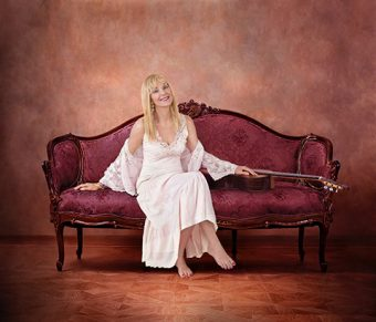 Photo of Liona Boyd sitting beside a guitar on an antique couch