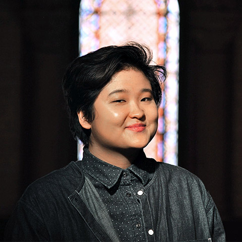 Head shot of Celeste Yim in a dark space in front of stained glass window