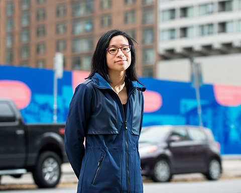 Ellen Tang in front of the St. John's Ward exhibit in downtown Toronto