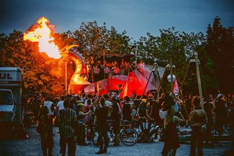 Photo of dragon breathing fire surrounded by a crowd of onlookers.