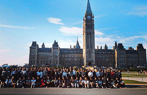 Photo of 100 female U of T students in front of a building on Parliament Hill.