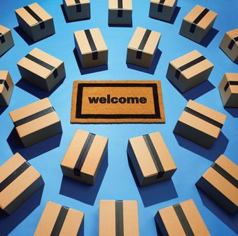 Photo of a welcome mat surrounded by concentric circles of sealed cardboard shipping boxes.