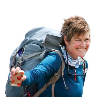 Photo of a smiling Alison Wiley carrying a large backpack and holding out a cellphone.