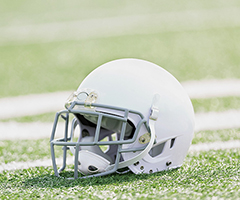 Photo of a football helmet lying upright on a football field.