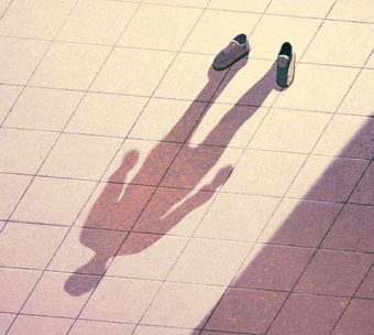 Illustration of a pair of shoes casting the shadow of a person.