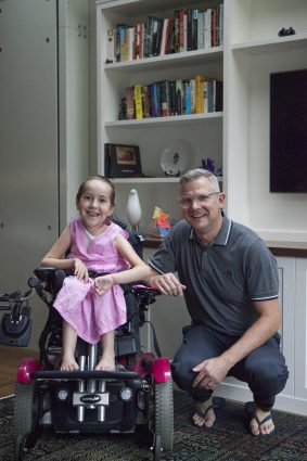 Prof. Ron Buliung crouches beside his daughter Asha, who is in a wheelchair, in their home