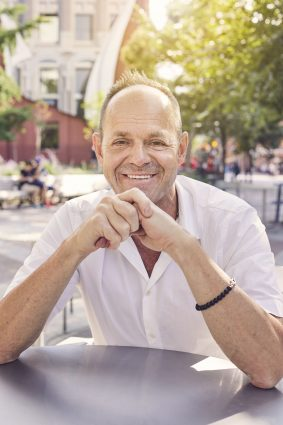 Claude Cormier sitting at table in Berczy Park, Toronto