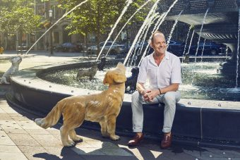 Claude Cormier sitting on edge of dog fountain he designed. He is beside a cast-iron golden retriever