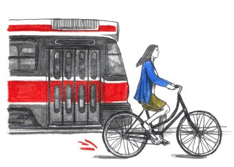 A owman on a bicycle rides alongside a Toronto streetcar