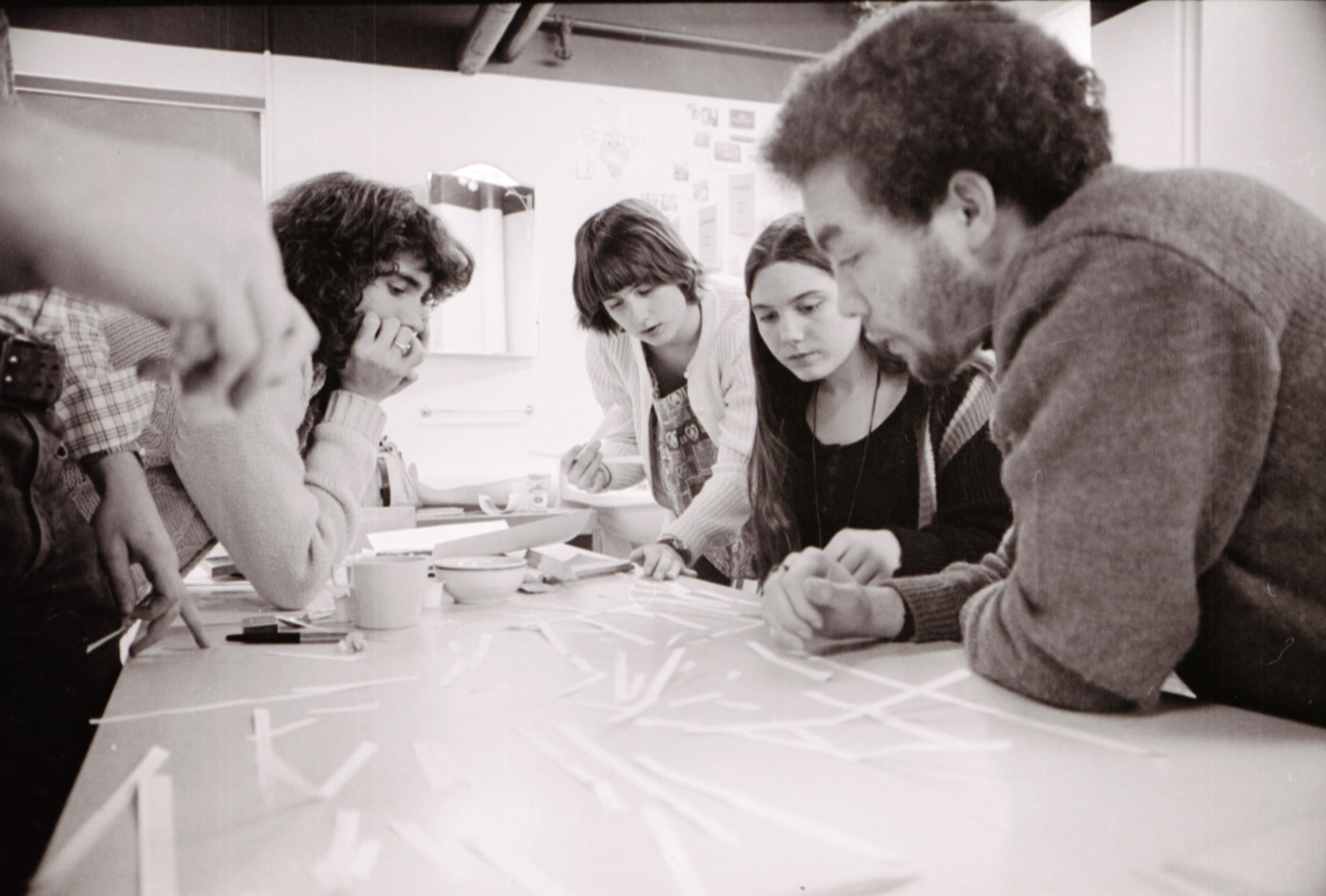 Four Cool School students gather around a table to work on a project together