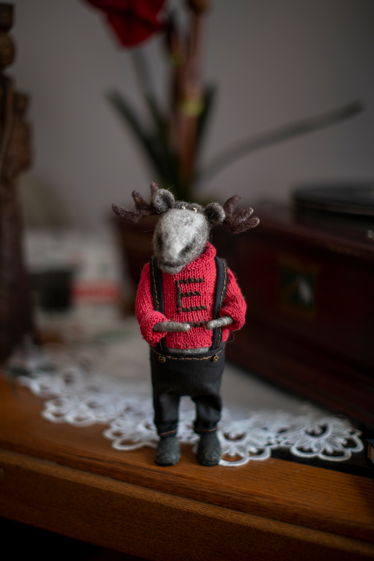 """A toy moose made of wool, wearing a knitted sweater with an embroidered """"E"""""""