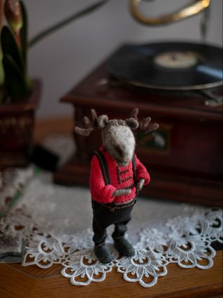 A small moose made out of wool stands on a wooden table next to a gramophone