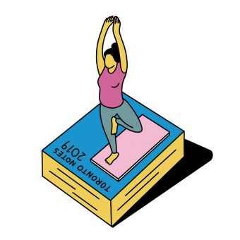 A woman doing yoga on a mat on top of a giant-sized Toronto Notes 2019 book
