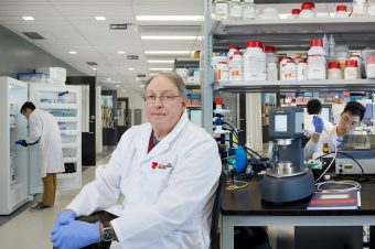 Prof. Paul Santerre in his lab at the Ted Rogers Centre for Heart Research, with his research team working in the background