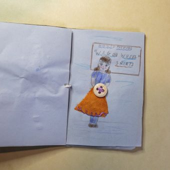 Open handmade book showing a drawing of a girl with a belt made of a button sewn into the drawing