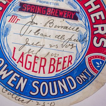 """Round label with words """"Spring Brewery,"""" """"Lager Beer,"""" and """"Owen Sound Ont"""" in all caps"""