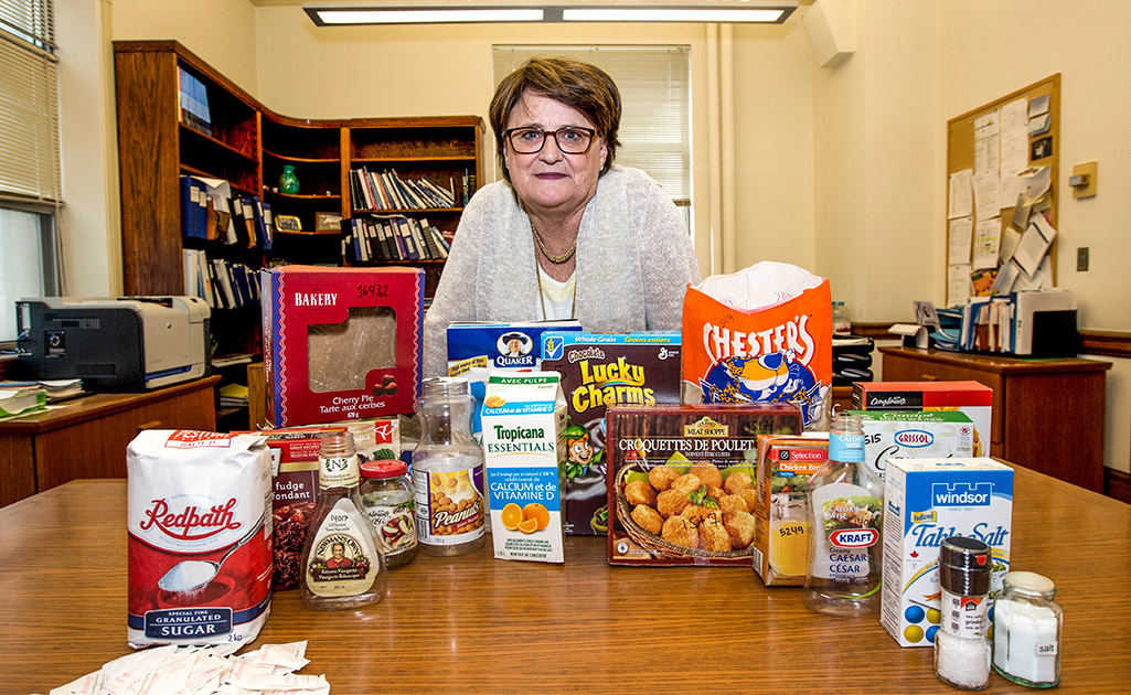 Prof. Mary L'Abbé standing behind a table of different packaged foods