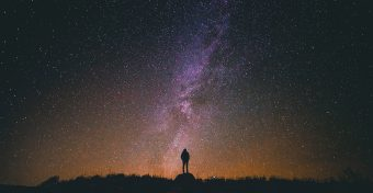 Small silhouette of a figure standing on a rock looking up at the night sky