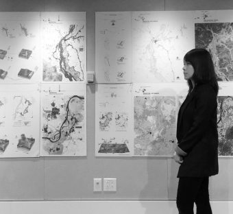 Shaine Wong looking at geological maps on a wall