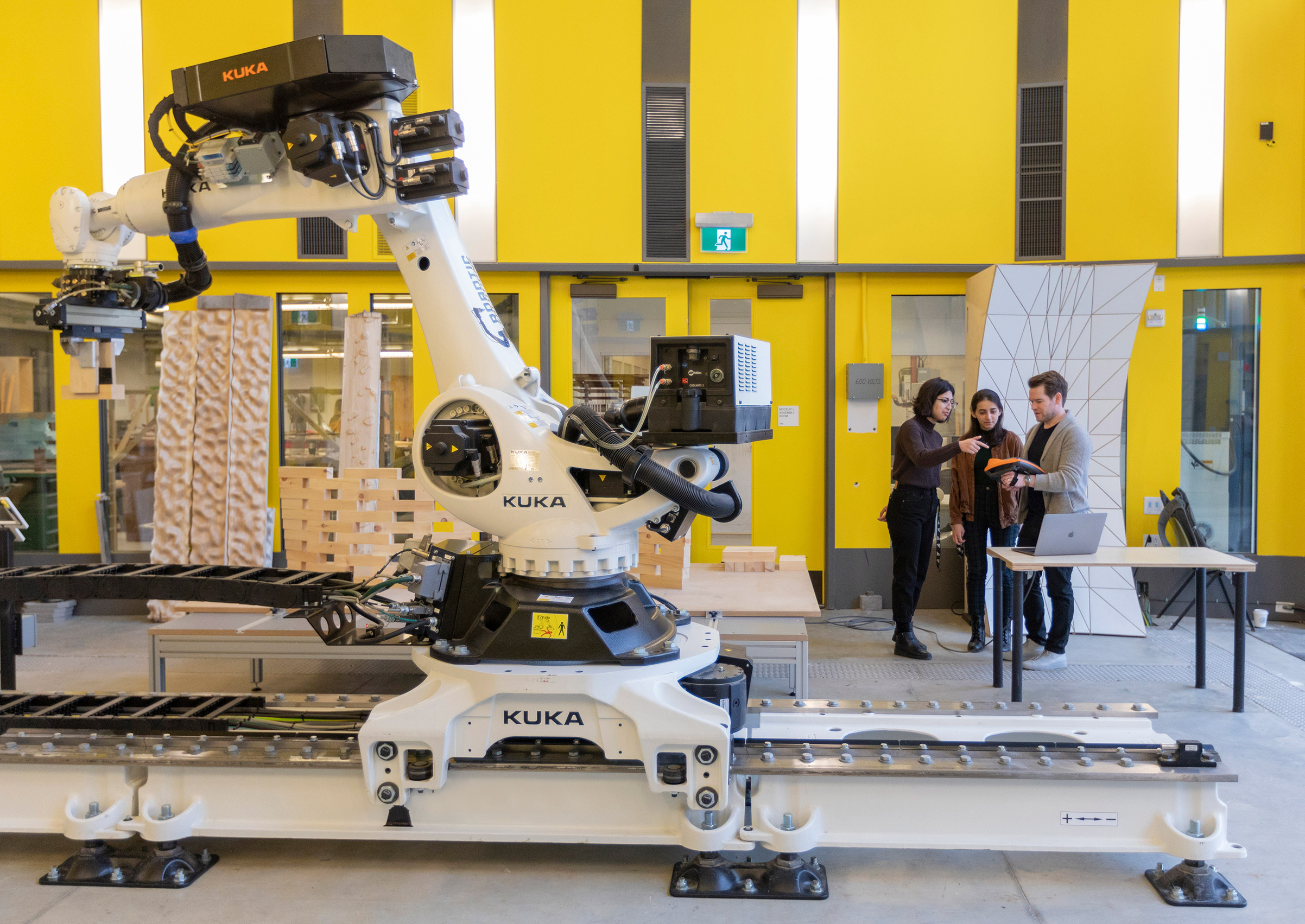 White robotic arm in the foreground against a yellow wall. Three students engaged in conversation in the background
