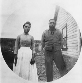 A black-and-white portrait of Mildred and John Ware, circa 1898, in front of their cabin