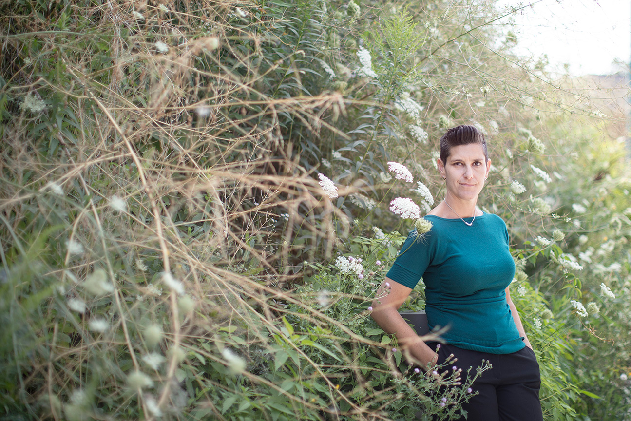 Prof. Jessica Green in a turquoise top standing in a clearing next to a forest of bushes, branches and white flowers