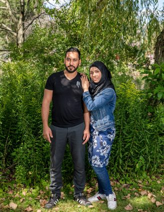 Alaa Al Saleh and Hanaa Al Bitar are standing in front of green bushes under leaves from a tree, looking at the camera. Bitar is turned toward Saleh with her hands on his left shoulder.
