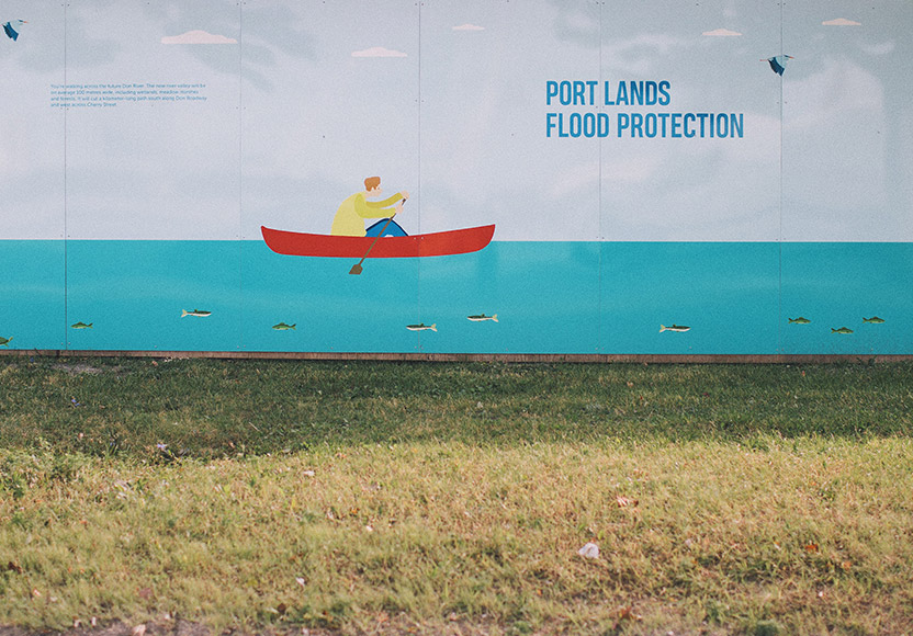 "Photo of a drawing of a person rowing a boat next to the words ""Port Lands Flood Protection"" on a wall erected on grass"