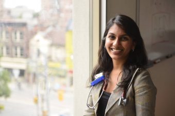 Close up photo of Ritika Goel, smiling with a stethoscope around her neck and standing in front of a window with a view of the street