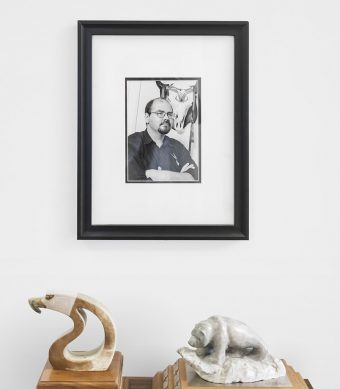 A framed black and white photo of Rodney Bobiwash hanging on a white wall above two awards, one a stone carving of an eagle and the other a stone carving of a grizzly bear on a rock, both on wooden plaques