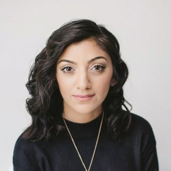 Headshot of Sadiya Ansari wearing a black top against a white studio background