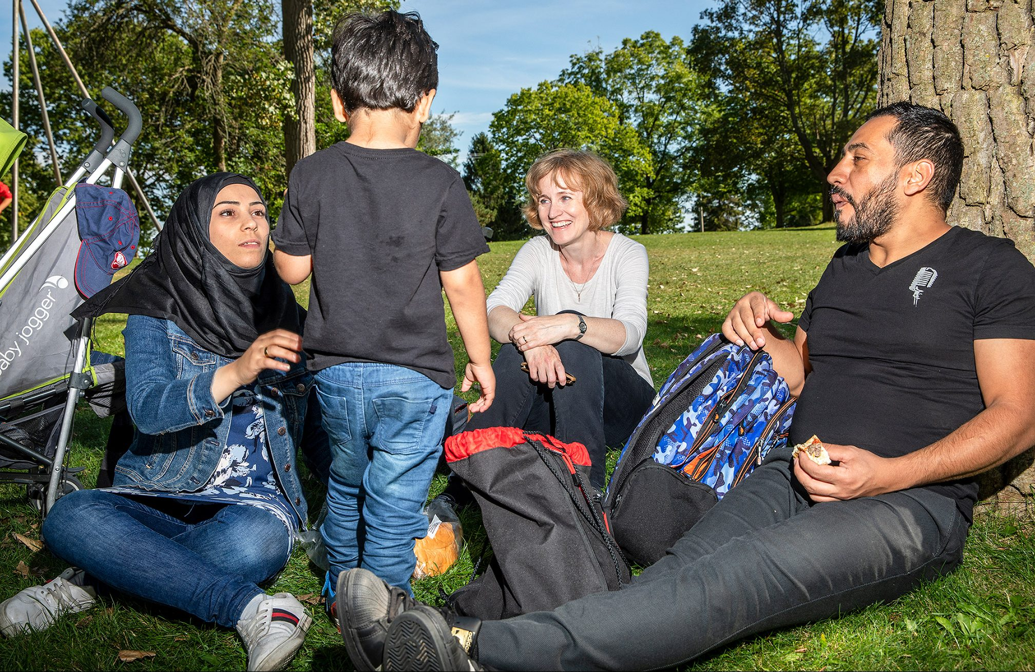 Hanaa Al Bitar, Jennifer Nagel and Alaa Al Saleh are sitting in a grassy field on Centre Island, looking at Mohamad Al Saleh, who is standing. Nagel is smiling and Saleh is leaning against a tree.