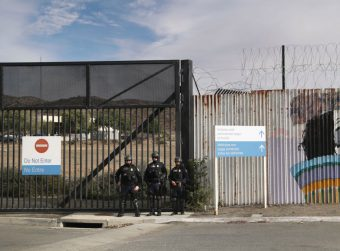 Three U.S. Customs and Border Protection officers stand in front of a gate next to a Do Not Enter sign.