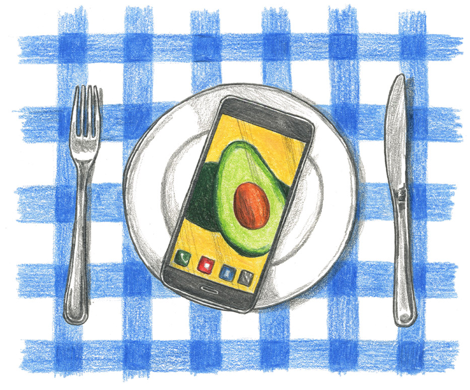 A fork, plate and knife are set out over a blue and white checkered tablecloth, with a cellphone on top of the plate with a picture of an avocado on the screen
