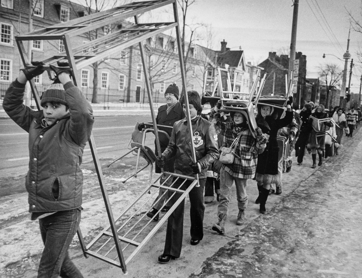 Black and white photo of students marching in line and carrying chairs. Two students upfront are carrying a metal rack.