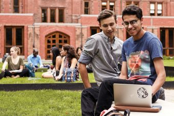 Students Quinn Underwood and Swarochish Goswami are working on a laptop while seated on a bench outdoors. Other students are sitting on grass in the background.