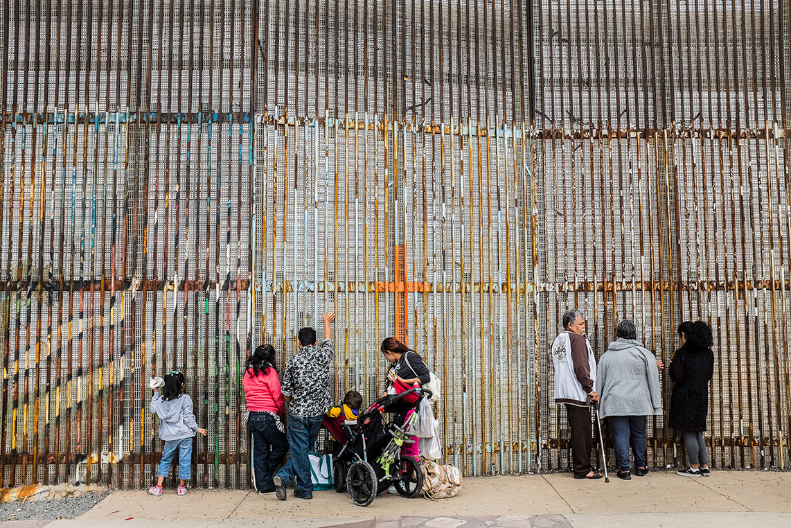 In the foreground, a family of five, with two young girls and a toddler in a stroller, stand facing the border gates in the background. An elderly couple and another adult stand a few feet away also facing the gates.