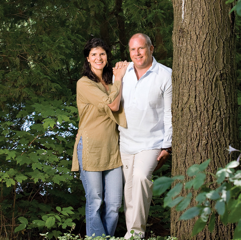 Alessandra and Paul Dalla Lana standing beside a tree with Alessandra's arms clasped around Paul's shoulder