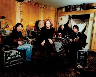 Group photo of Cowboy Junkies' Michael Timmins, Peter Timmins and Alan Anton sitting with their instruments, with Margo Timmins seated front and centre