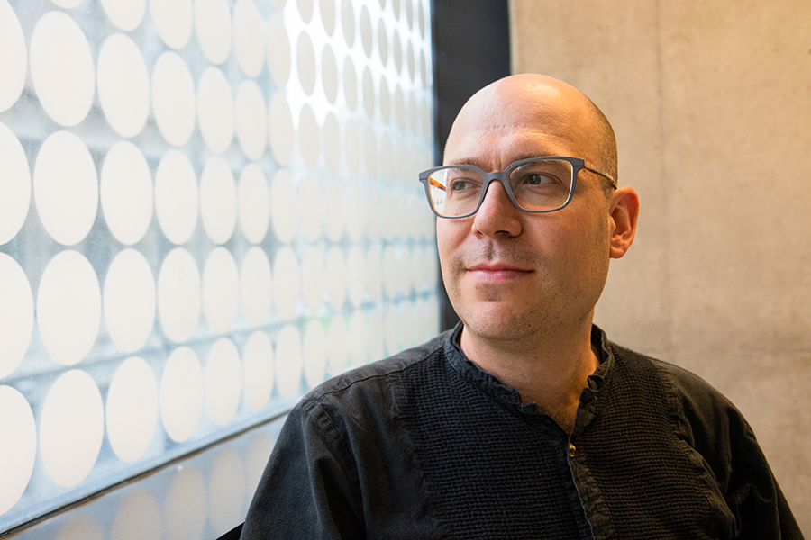 Headshot of Prof. Aspuru-Guzik looking out of a window on the left side of the photo