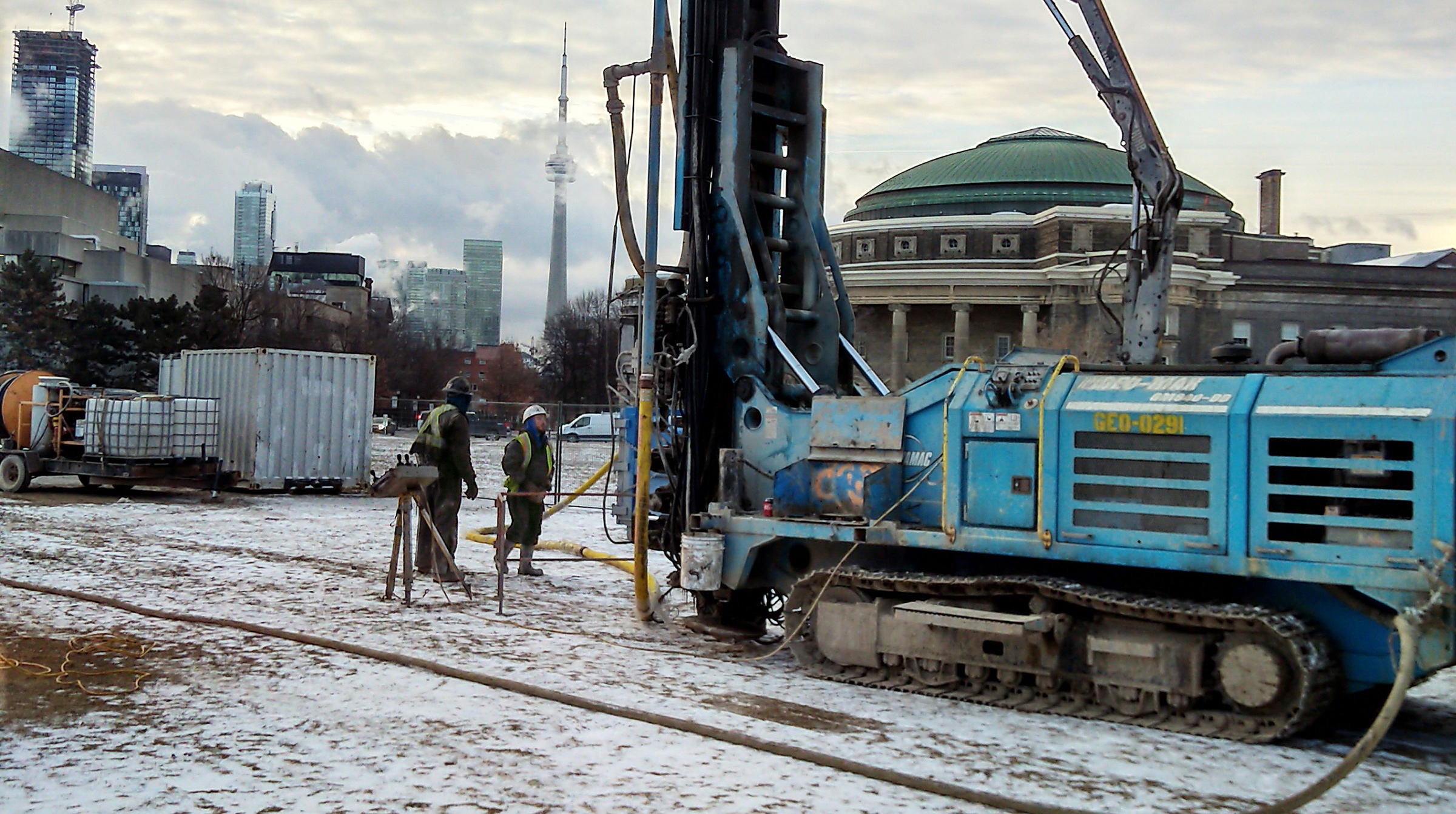 Two workers standing in front of a tank-like machine drilling a hole into the ground of the front campus field