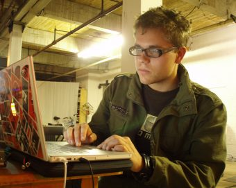 Eliot Britton operating his laptop in a large studio space
