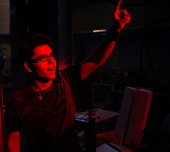 Teenaged Eliot Britton standing with one arm raised and finger pointing upward, bathed in red light