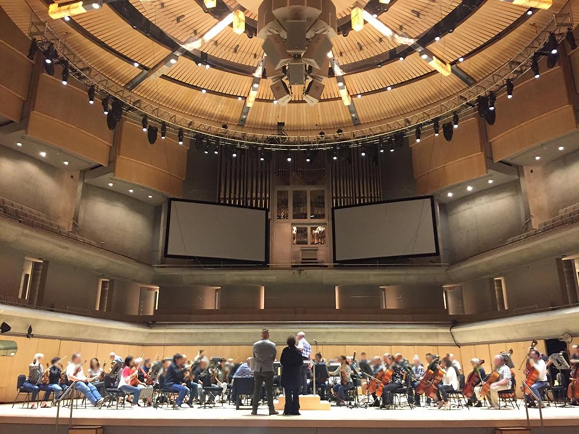 The Toronto Symphony Orchestra rehearsing onstage with two projection screens overhead, and Eliot Britton and Sandra Laronde observing from front of the stage