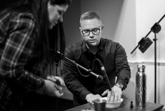 Eliot Britton sitting with his hand in a small bowl on a table underneath a microphone; a student stands slightly bent over beside him observing