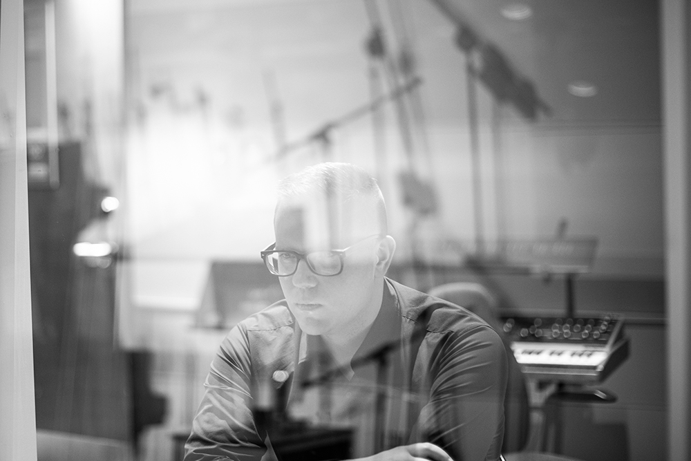 Black and white photo of Eliot Britton sitting in a music studio behind glass that is reflecting rod-like shapes