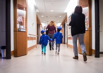 Two young children in blue uniform holding hands and walking behind and in front of two women down a hallway